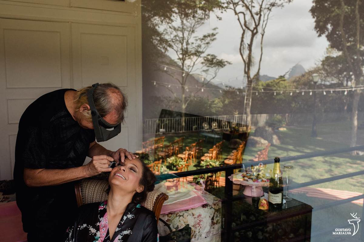 maquiador passando sombra na noiva enquanto o pão de açúcar aparece no reflexo da janela