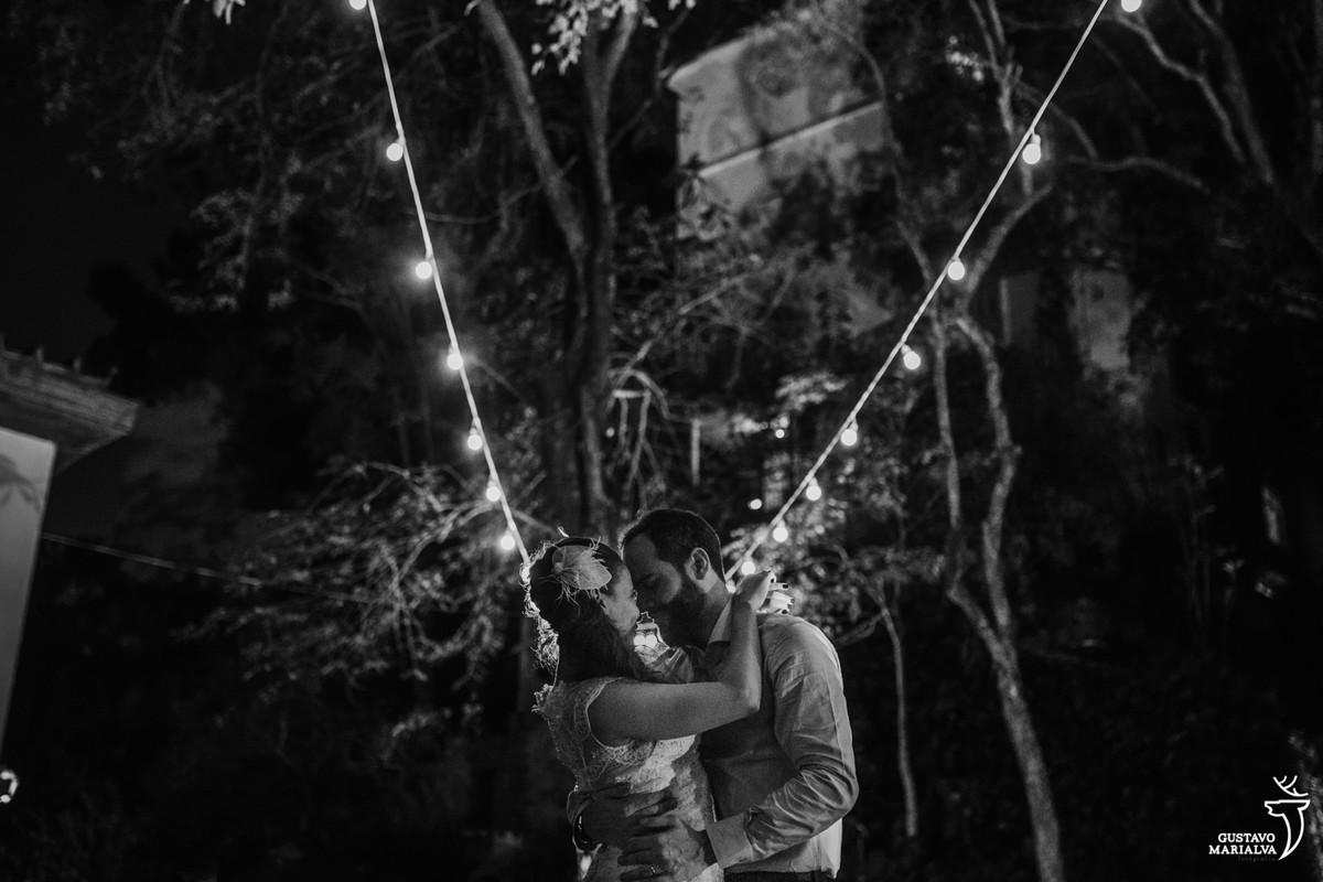 casal abraçado posando para retrato com as gambiarras áreas nas árvores no recanto do barão