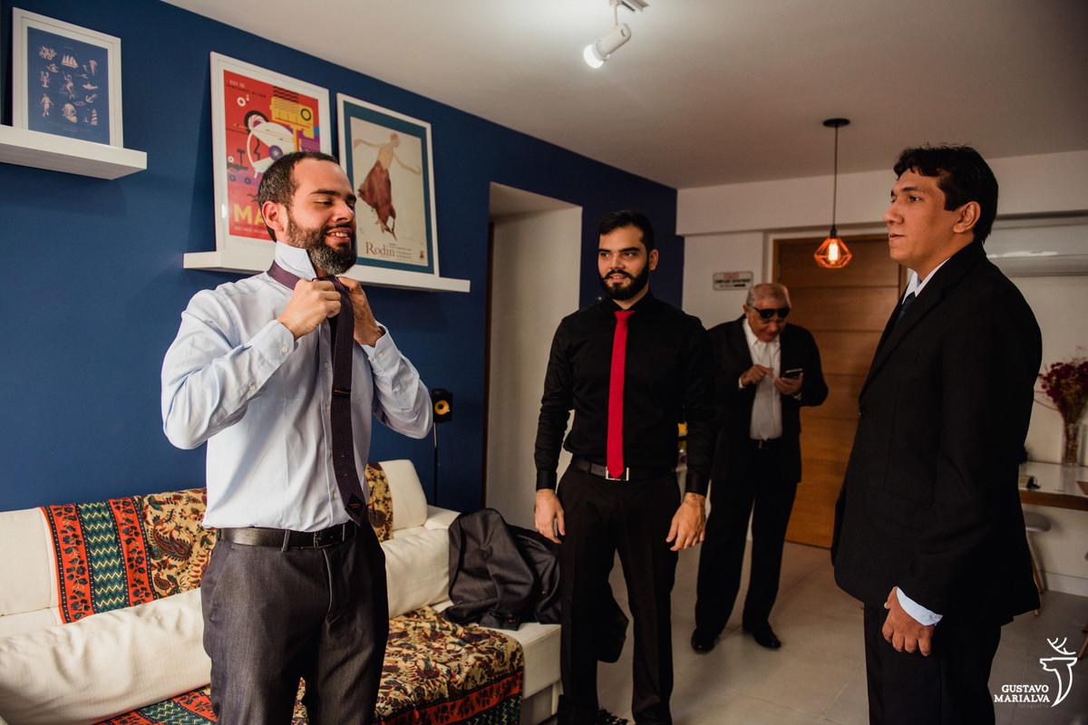 noivo colocando a gravata sendo observado pelos irmãos e pai