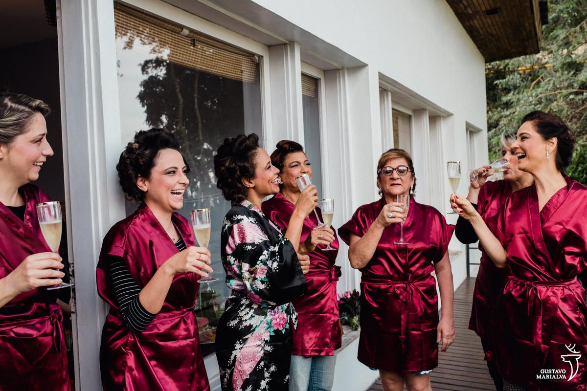 noiva e madrinhas brindam sorrindo com copo na mão no making of do casamento