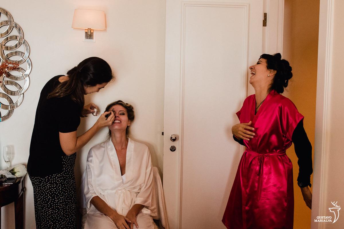 noiva sendo maquiada e madrinha rindo no making of do casamento no copacabana palace