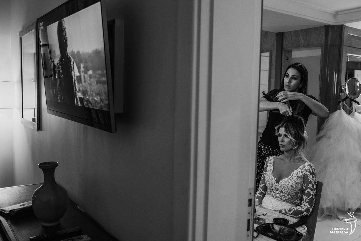 noiva arrumando cabelo no banheiro  com show do mick jagger passando na tv