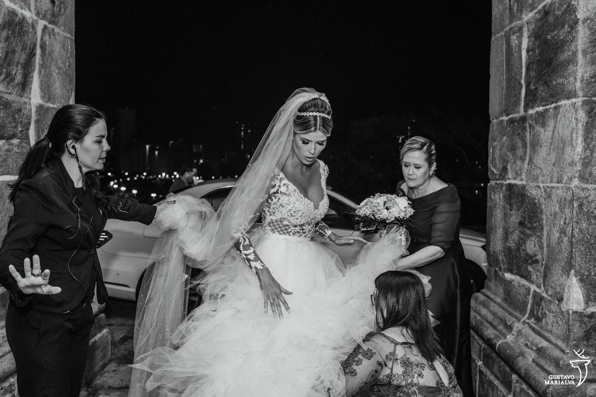 mãe e tia da noiva arrumando o vestido antes de entrar na cerimônia do casamento no outeiro da glória