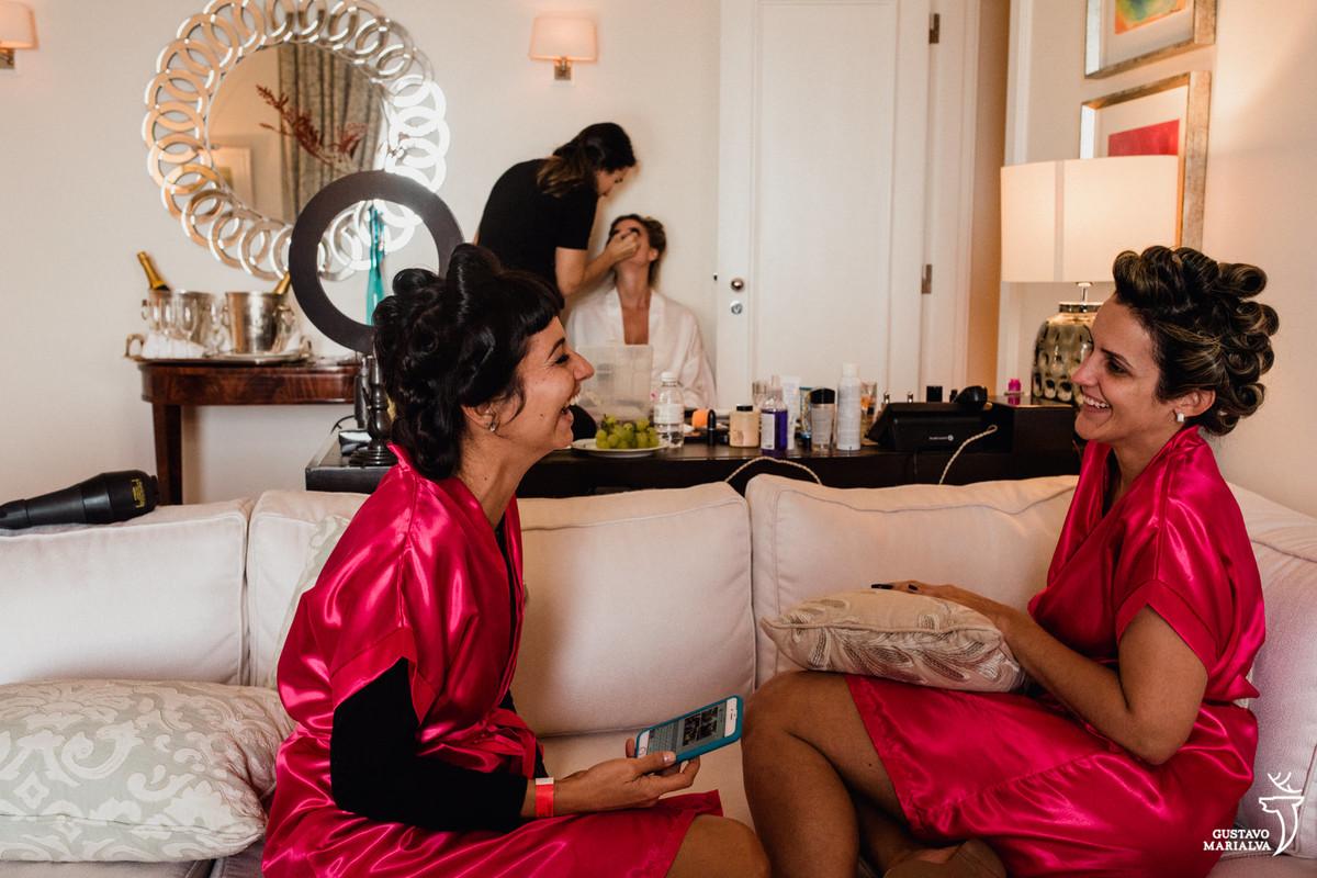 madrinhas conversam sorrindo enquanto noiva é maquiada durante o making of do casamento no copacabana palace
