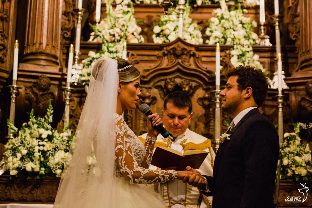 noiva lendo os votos segurando a mão do noivo na cerimônia do casamento