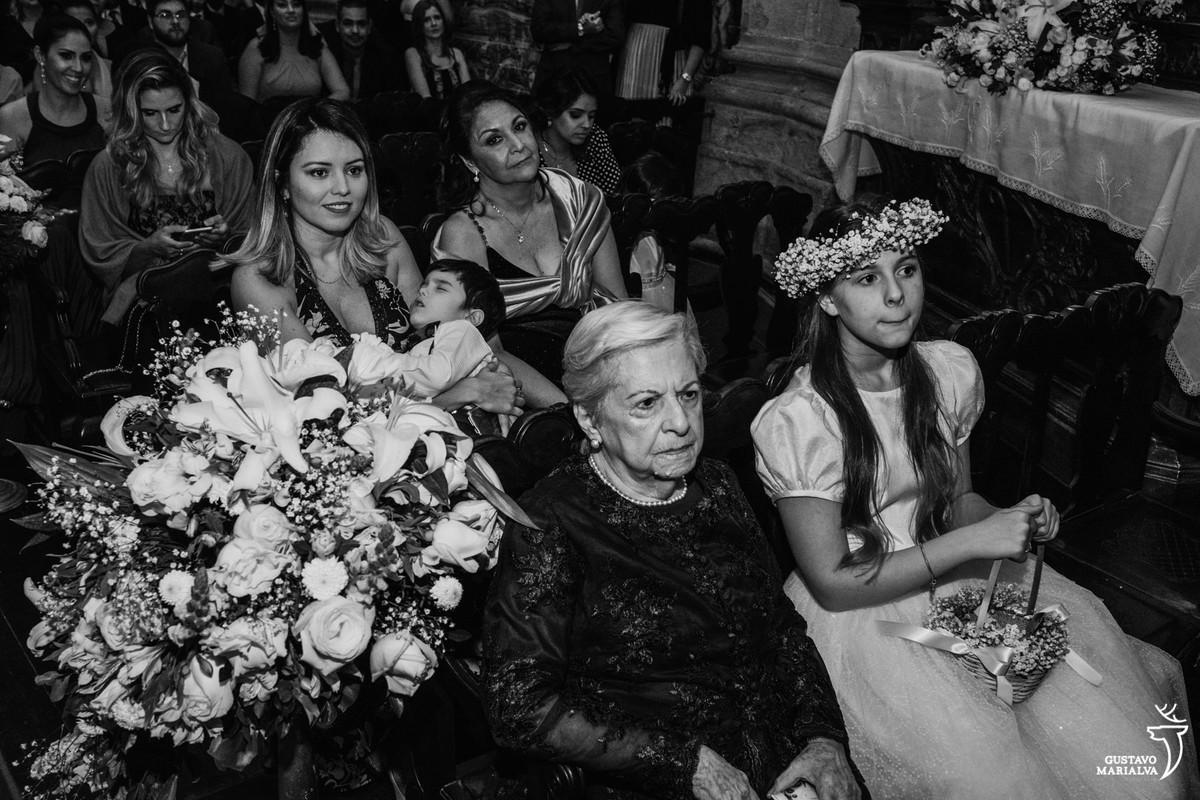 menino dorme no colo da mãe e senhora e daminha observam a cerimônia de casamento