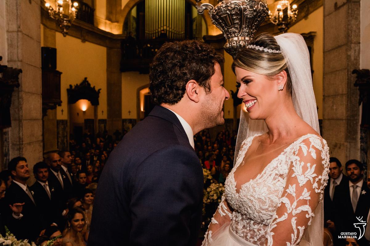 noivos sorriem de rosto colados na cerimônia de casamento