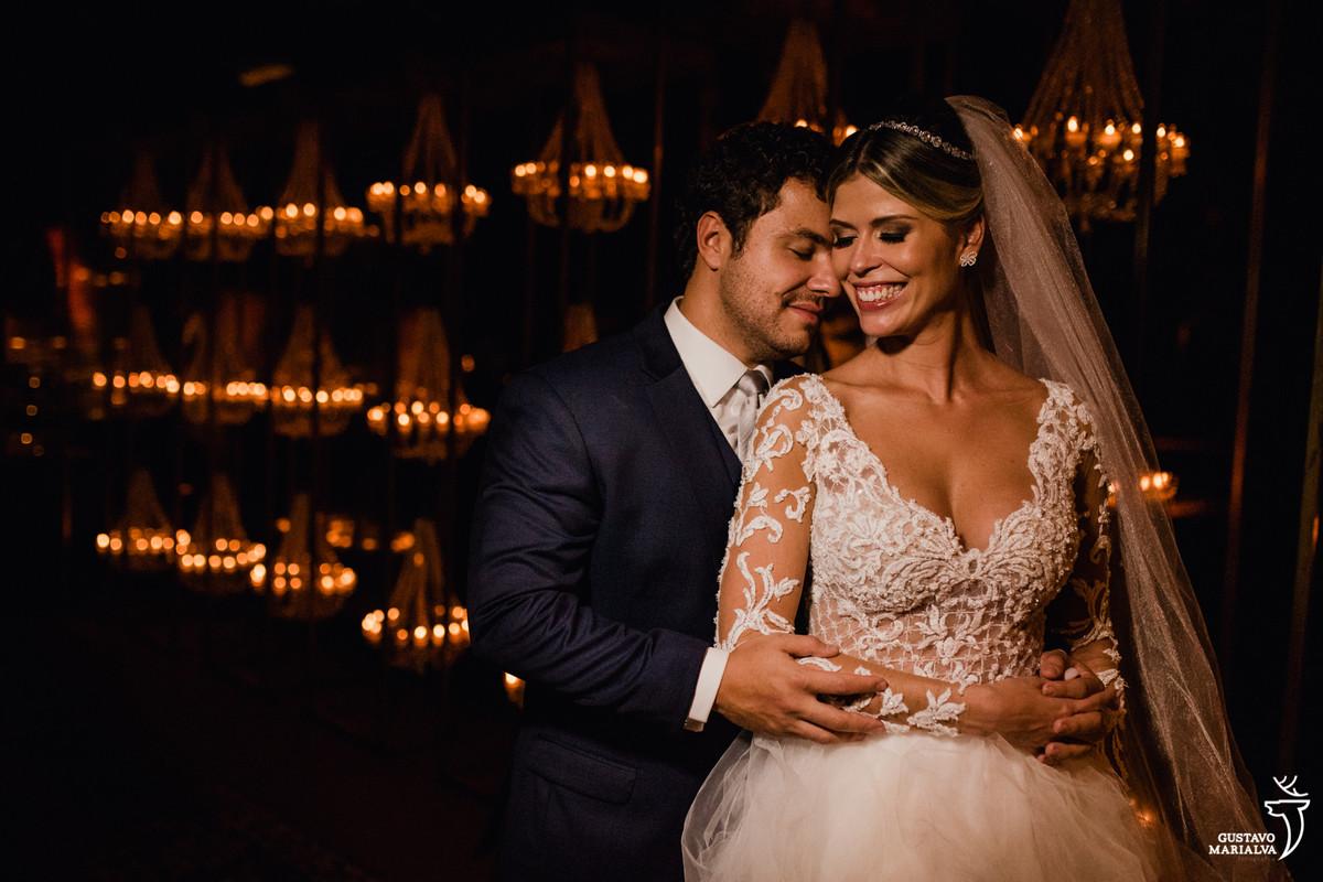 noivo abraça a noiva por trás que sorri com parede de velas ao fundo