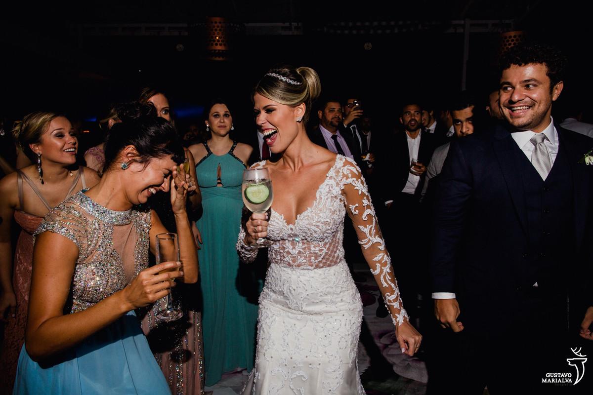 noiva sorri e dança com drink na mão enquanto madrinha coloca a mão no rosto