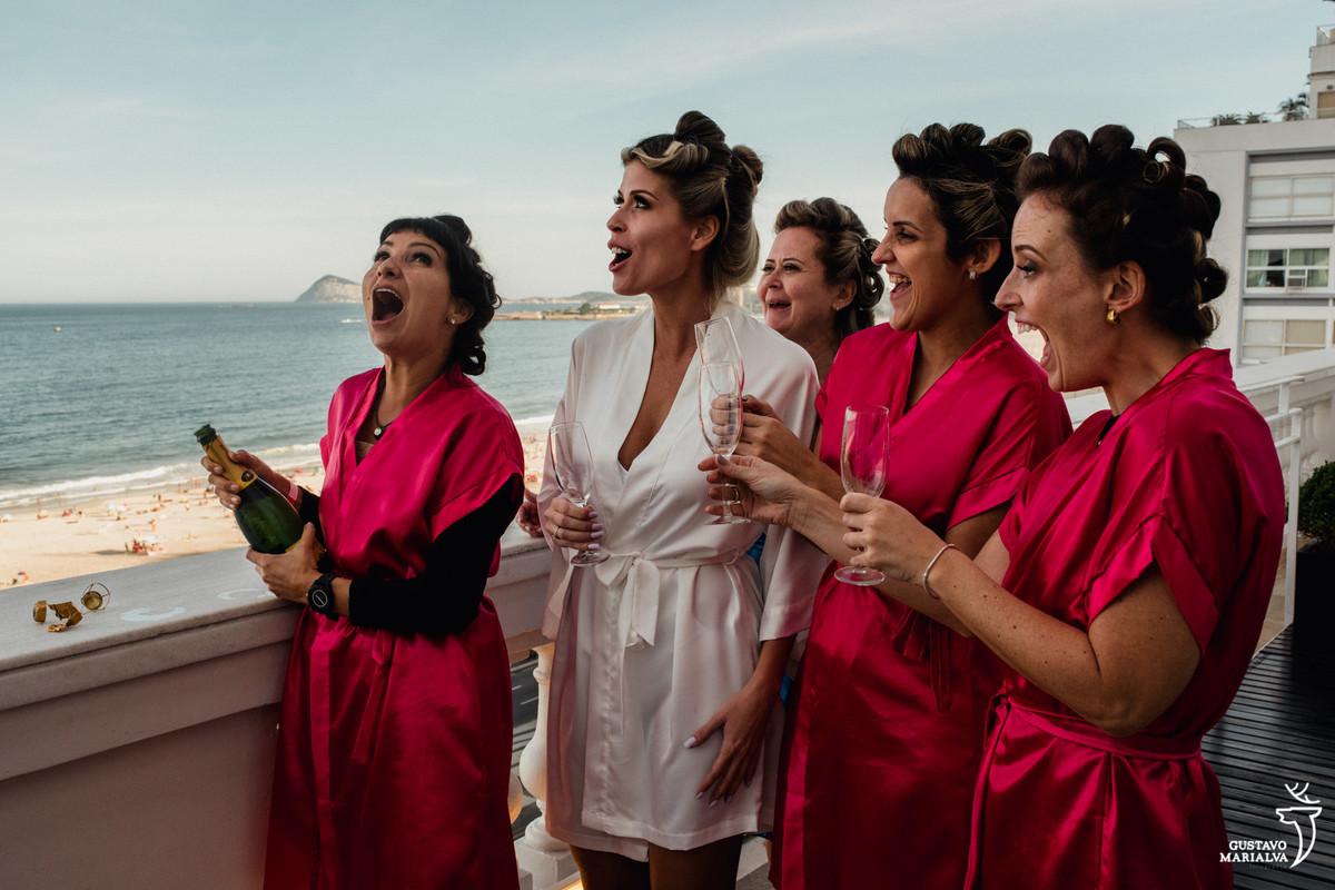 madrinha om a boca aberta estoura a champanhe na varanda do copabana palace e noiva e migas sorriem