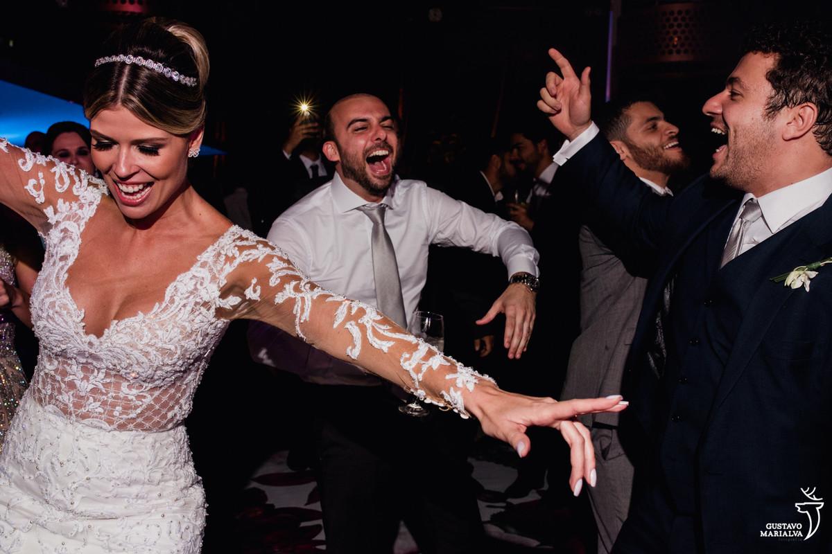 noiva dançando com os braços abertos e amigos sorrindo ao fundo