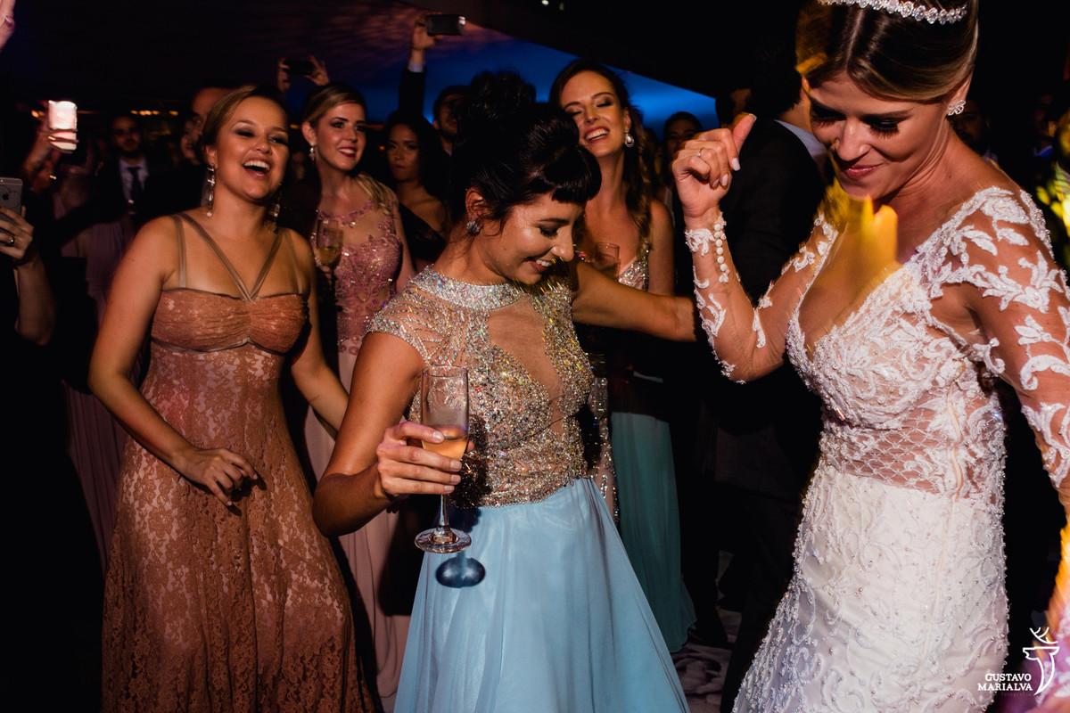 noiva dançando funk com madrinha segurando copo e sendo observada pelas amigas sorridentes