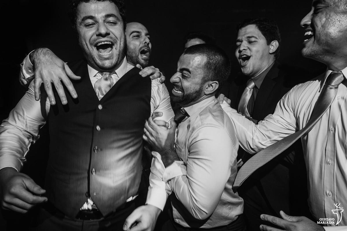 amigos abraçam o noivo e fazem careta