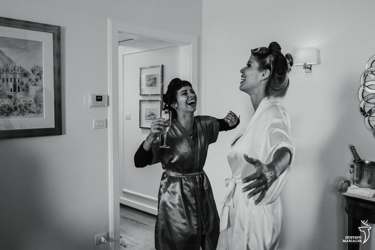 noiva dança com madrinha sorrindo e com copo na mão durante o making of do casamento no copacabana palace