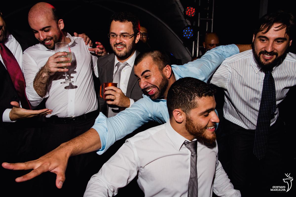 amigos dançam em cima do palco e homem faz careta com o copo na mão
