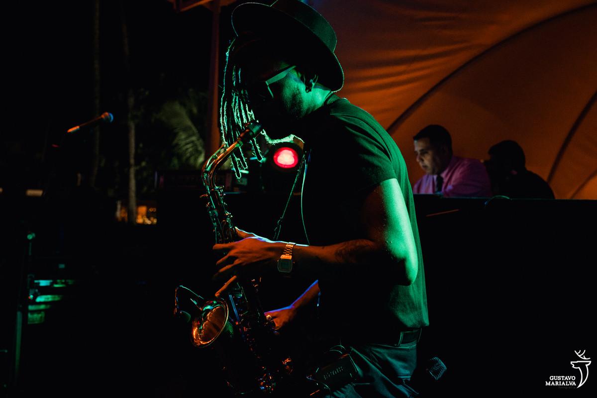 homem toca saxofone no palco