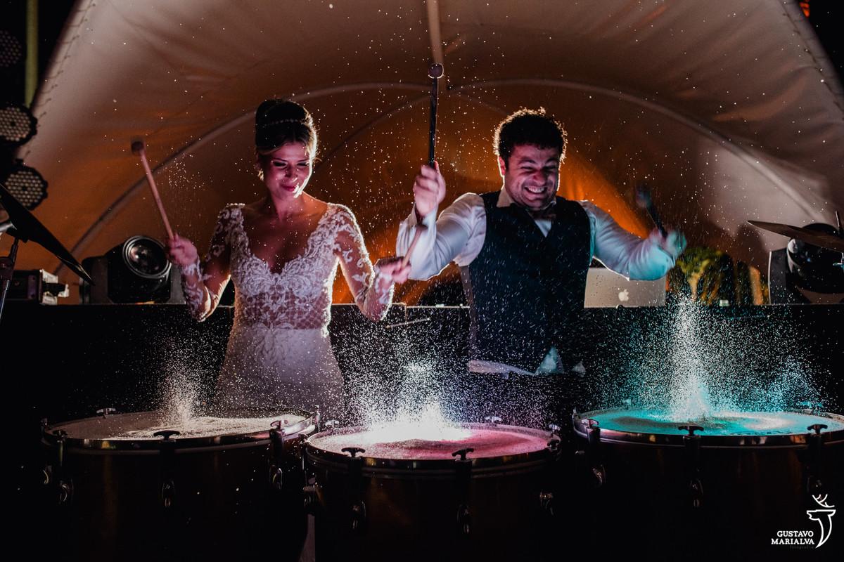 noivos tocam tambor no palco com areia pulando