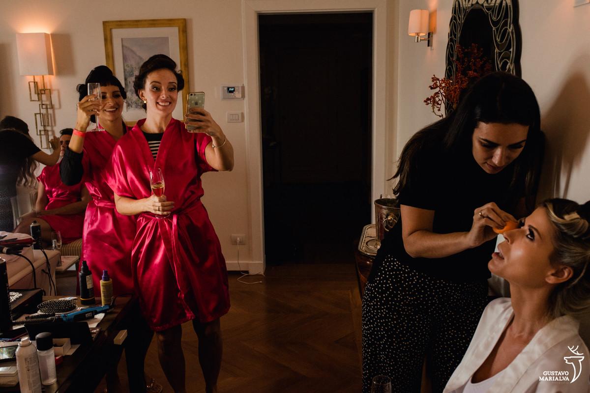 Madrinas tiram foto com o celular da noiva sendo maquiada