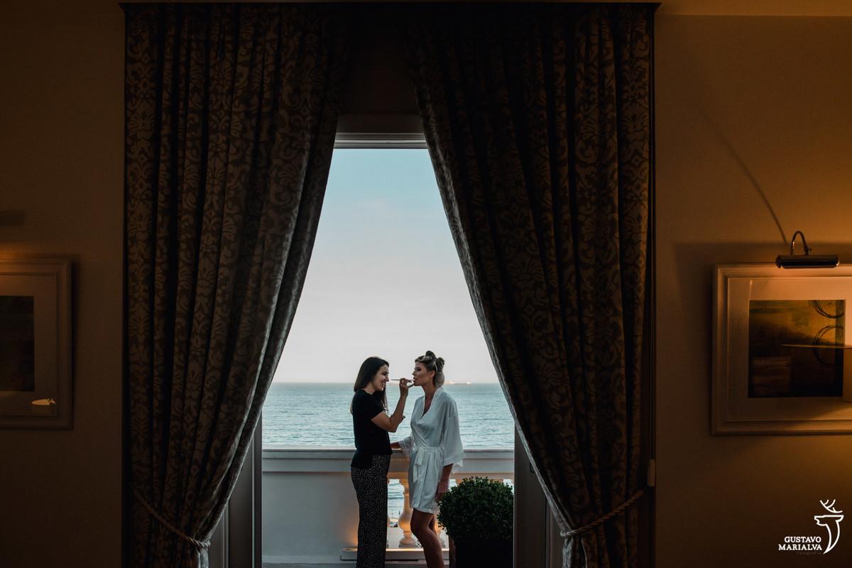 noiva é maquiada na varanda do copabana palace com a praia de copabana ao fundo