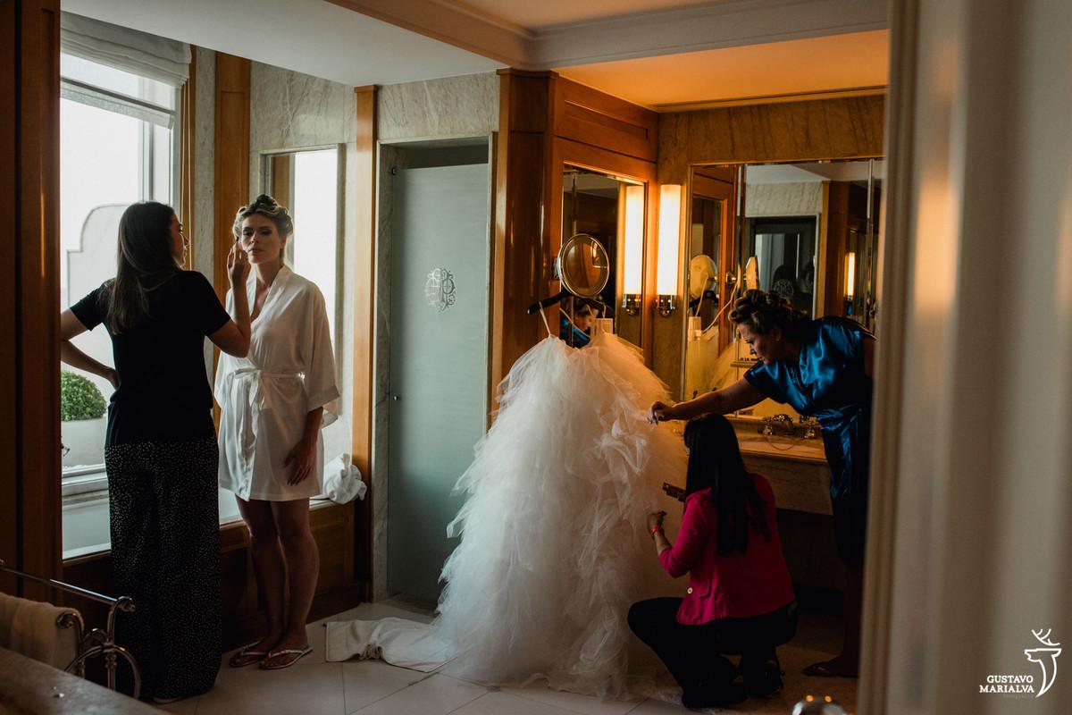 noiva é maquiada enquanto mãe e madrinha ajeitam o vestido de noiva da carol hungria no banheiro do copabana palace