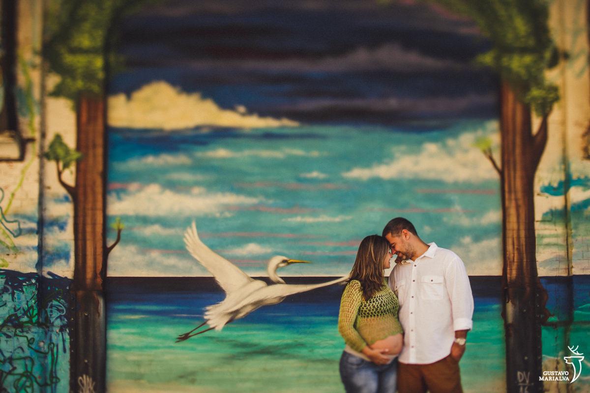 casal de grávidos se abraça em frente a parede com desenho de uma cegonha