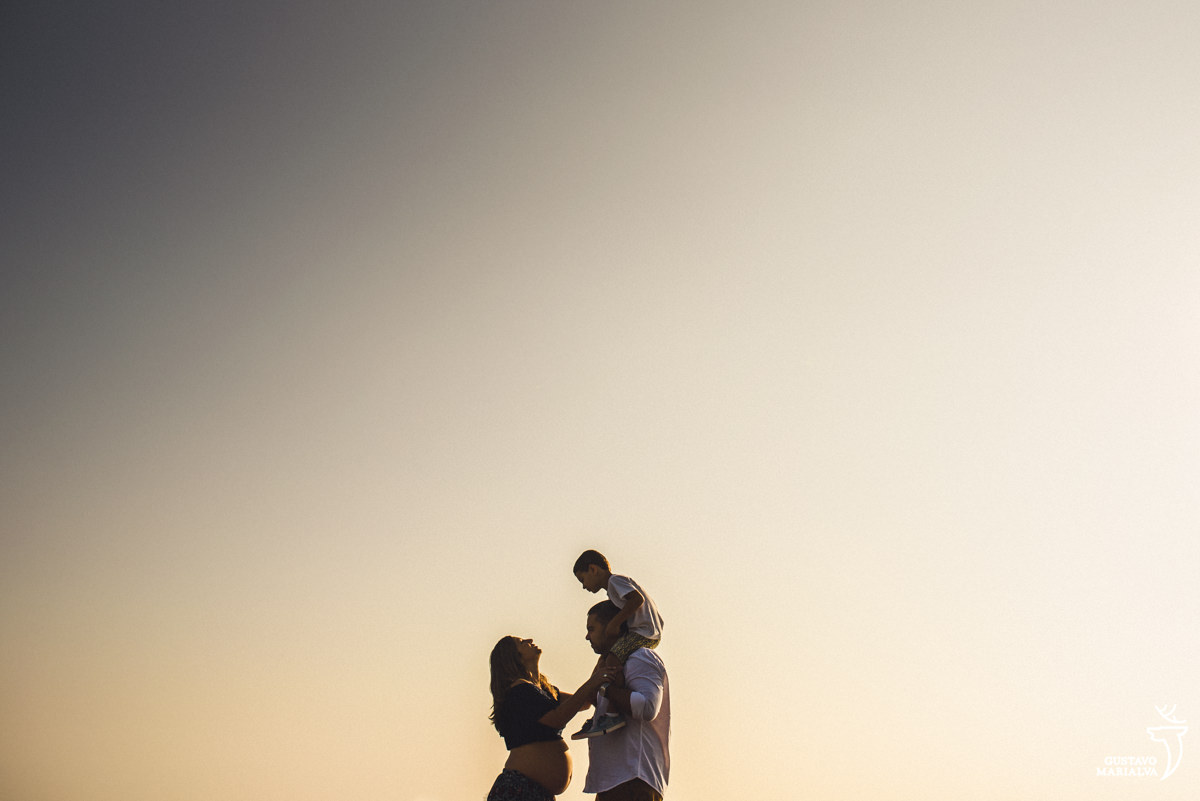 gestante abraça homem que carrega o filho nas costas