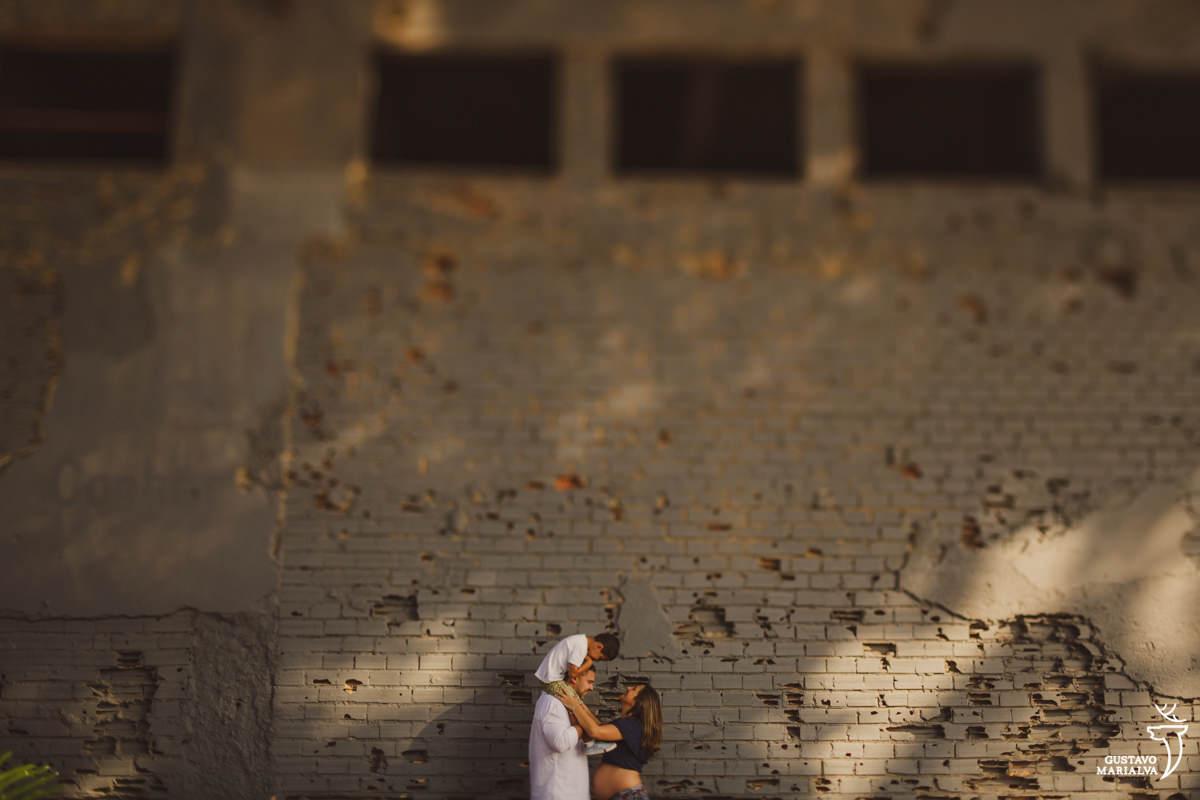 familia se abraça com criança nas costas em frente a parede detonada