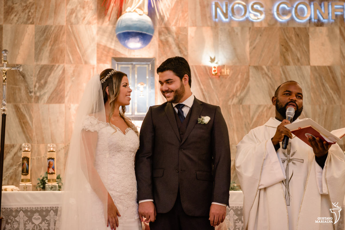 noivos trocam olhares enquanto padre comando a missa