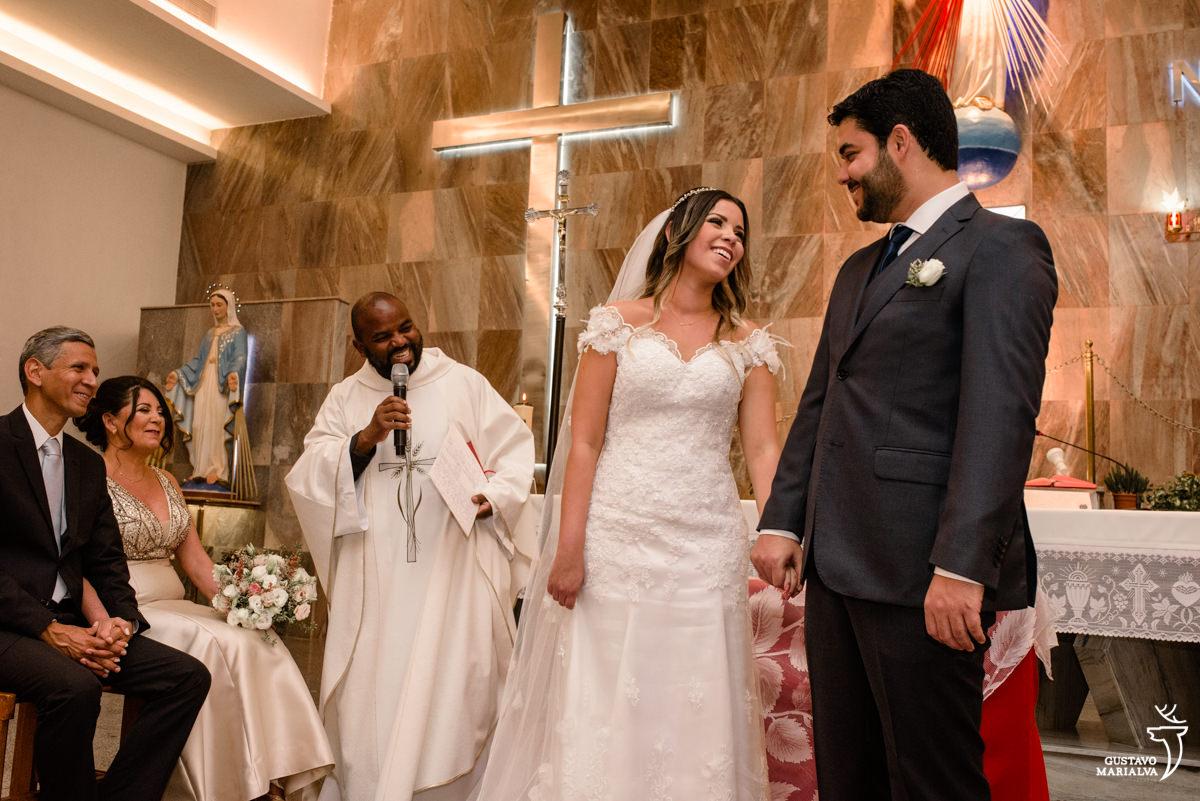 noivos de mãos dadas trocam olhares e sorriem enquanto são observados pelo padre e pais