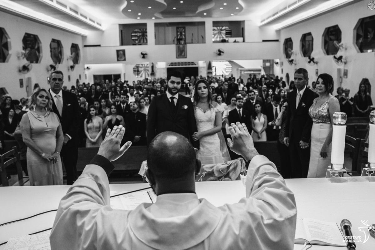 padre levanta os braços para abençoar os noivos