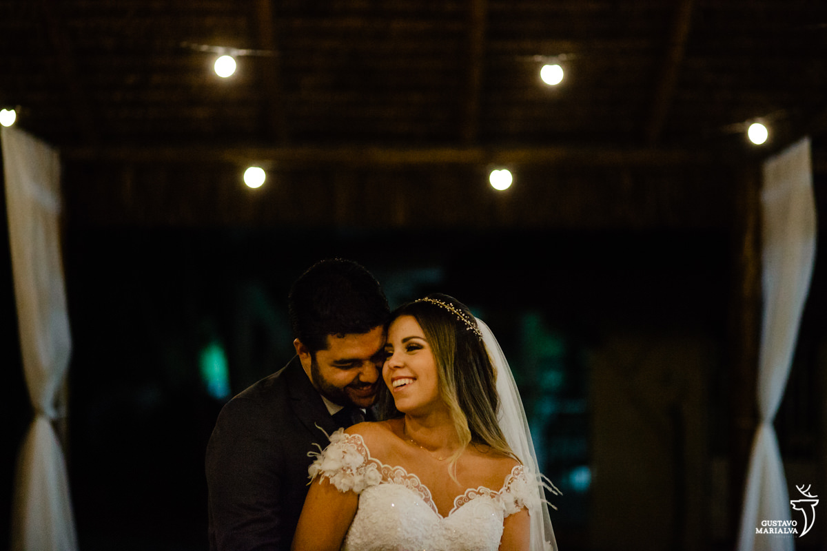 noivo abraça a noiva por trás que sorri