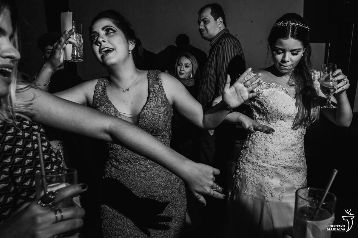 noiva e amiga dançam de braços abertos na pista de dança do casamento