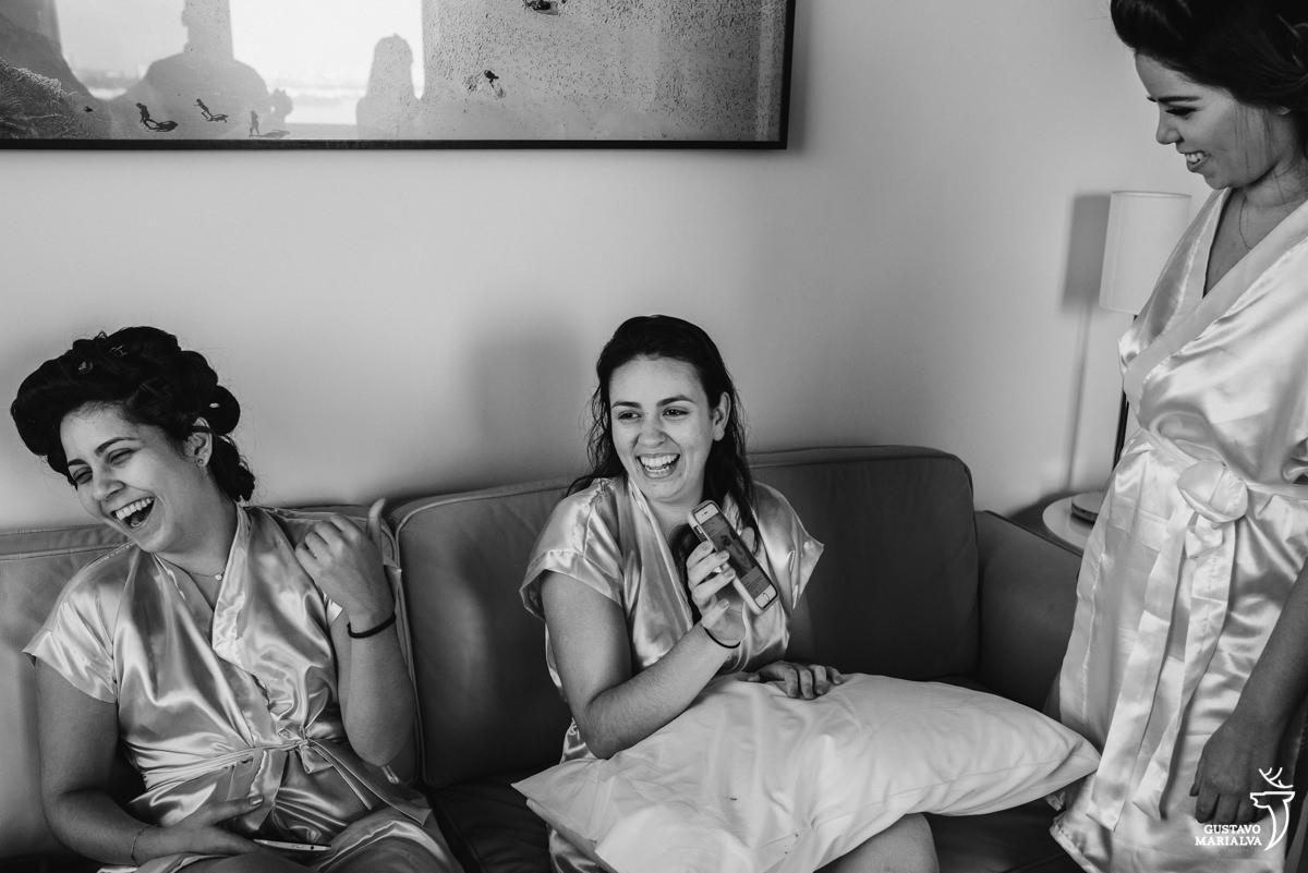 madrinha ri apontando para a outra madrinha q ri e mostra o celular para noiva