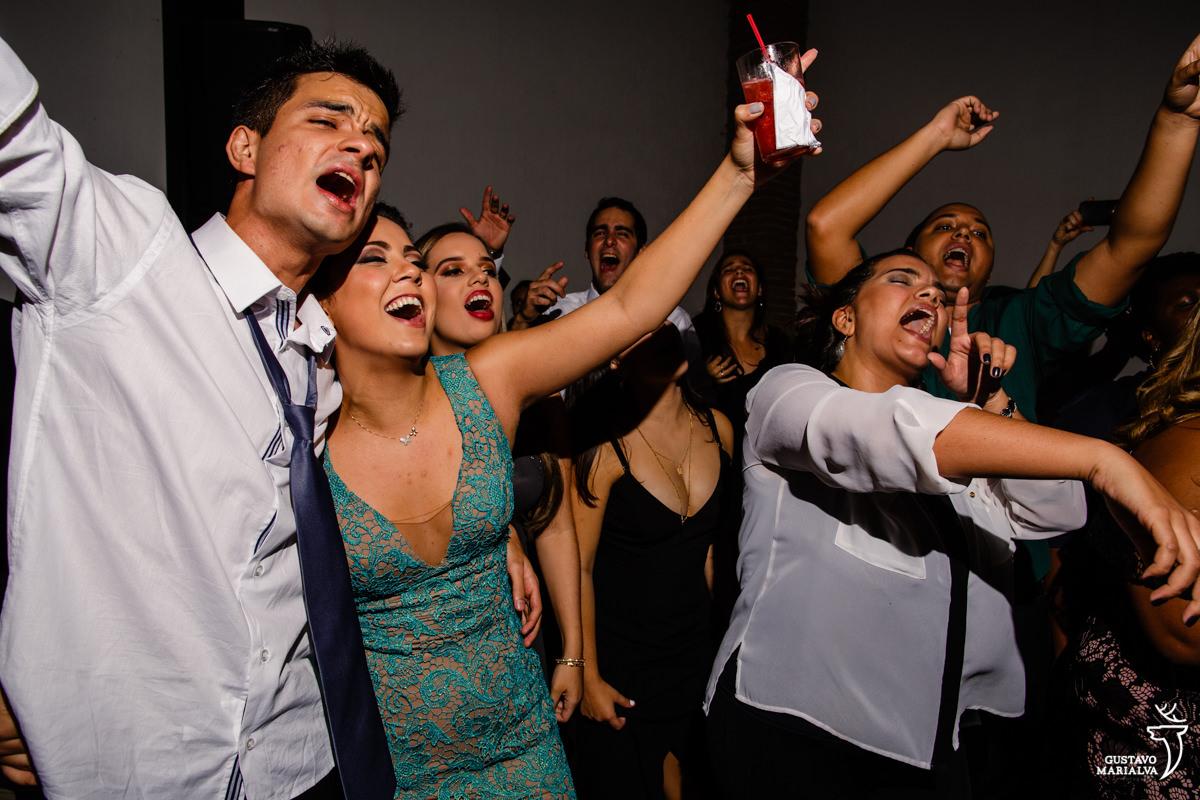 convidados dançam abraçados, cantando, enquanto amigos cantam com braços abertos