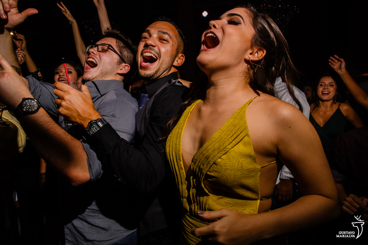amigos dançam abraçados enquanto mulher pula cantando com a mão na barriga