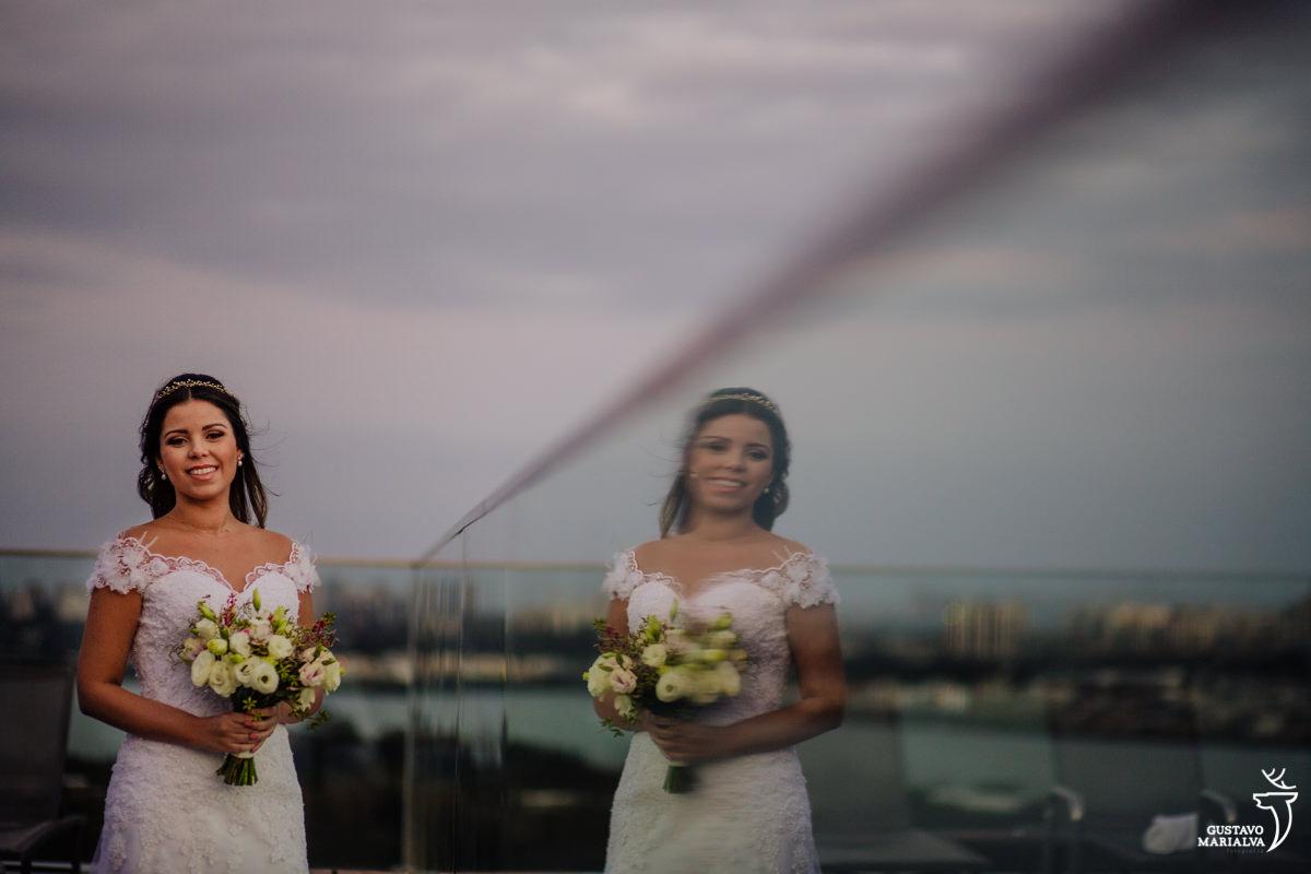 noiva segura buque e posa para retrato com reflexo no espelho