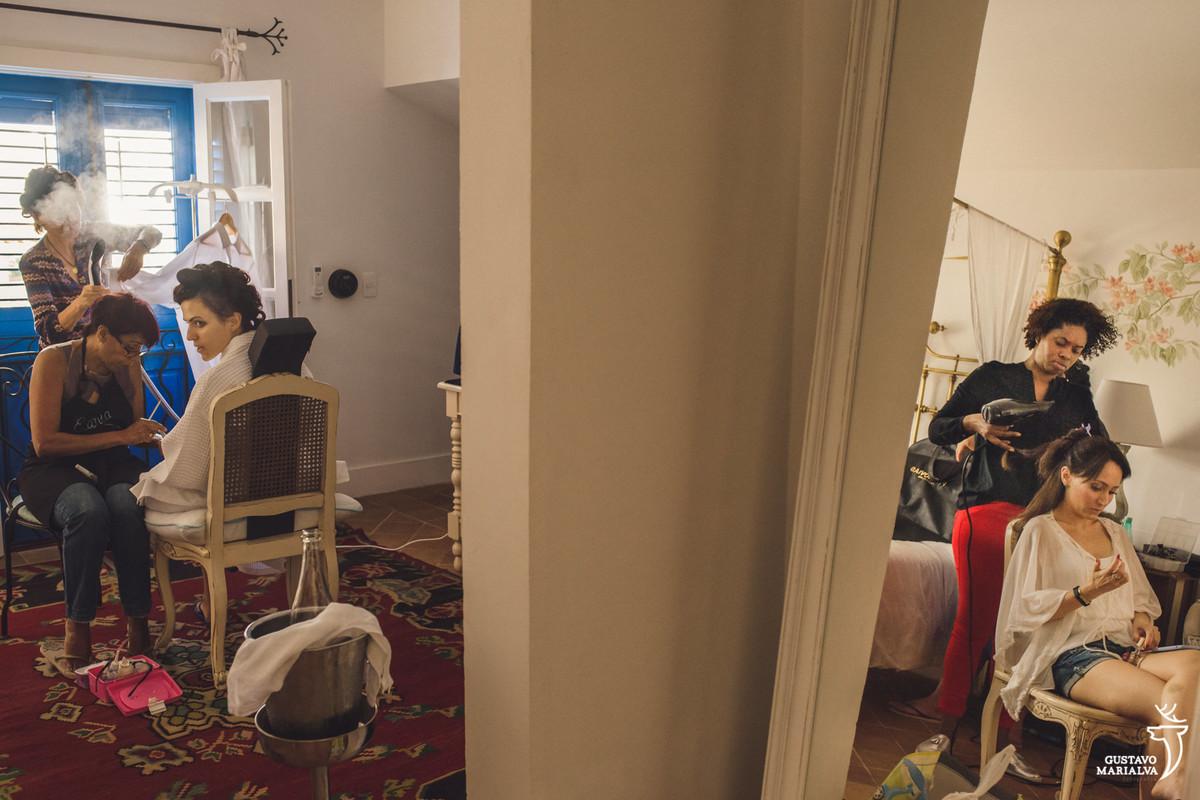 noiva fazendo a unha e olhando para trás enquanto a mãe passa o vestido de noiva e a irmã arruma o cabelo