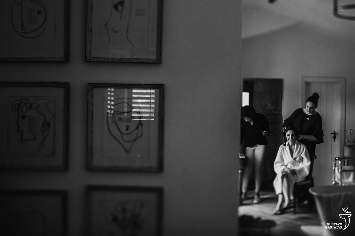 noiva sentada na cadeira se preparando para o casamento e uma série de quadros pendurados na parede do hotel vila da santa em búzios