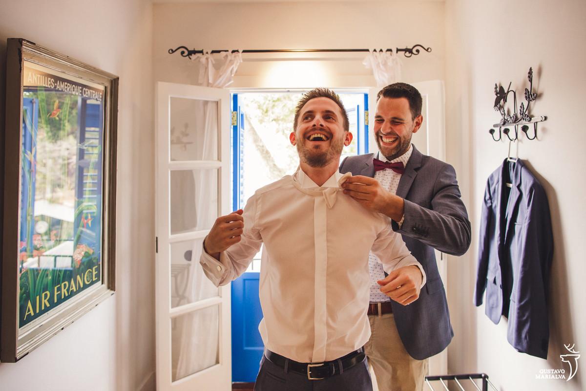 padrinho sorrindo ajuda o noivo a colocar a gravata borboleta que sorri