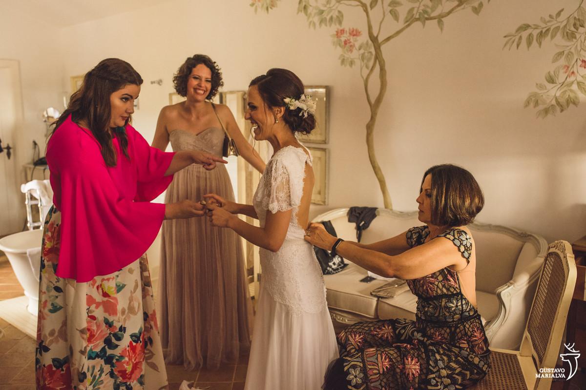 mãe da noiva fecha o vestido da noiva enquanto as amigas observam emocionadas e sorridentes