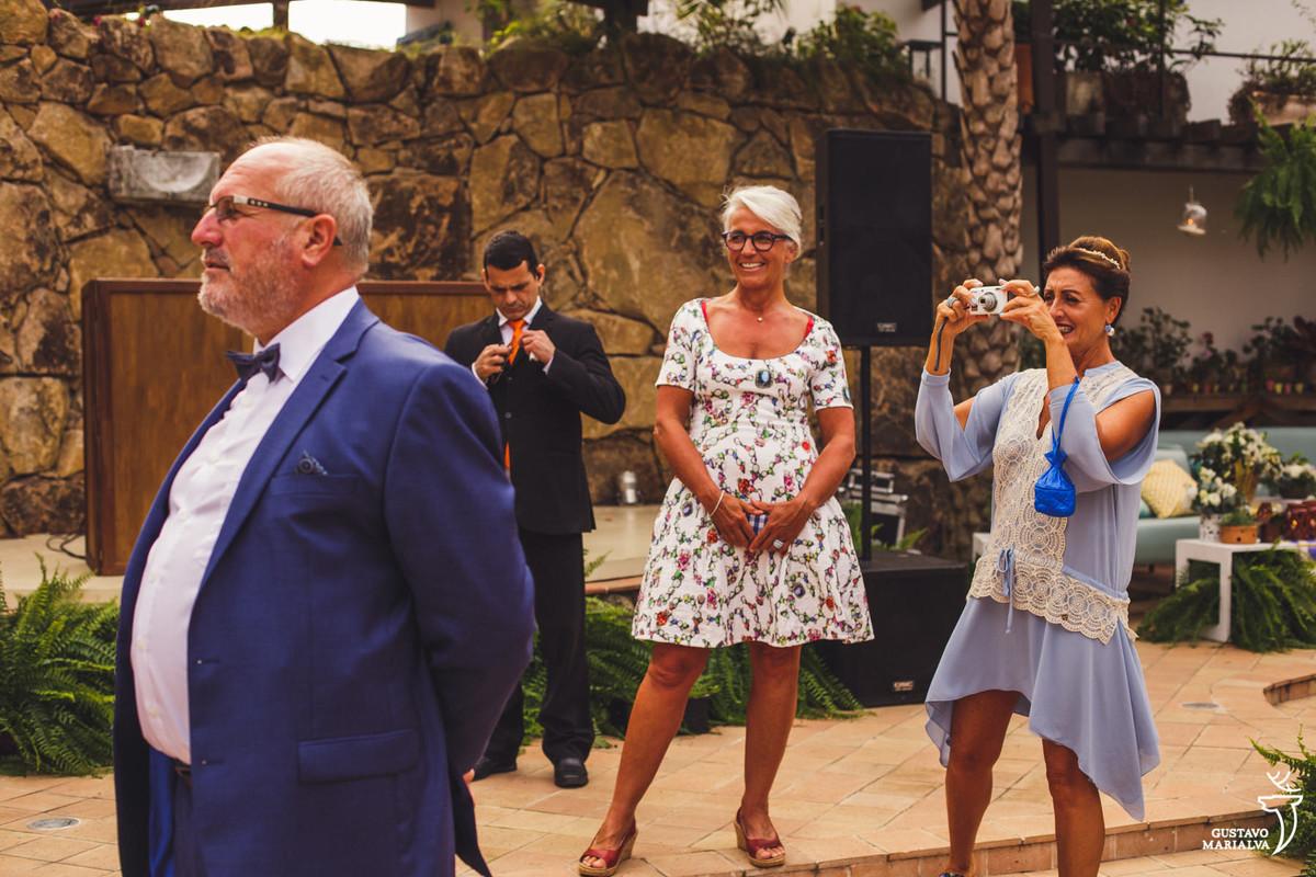 homem de terno azul e gravata borboleta observa a paisagem enquanto mulher tira fotos e outra sorri