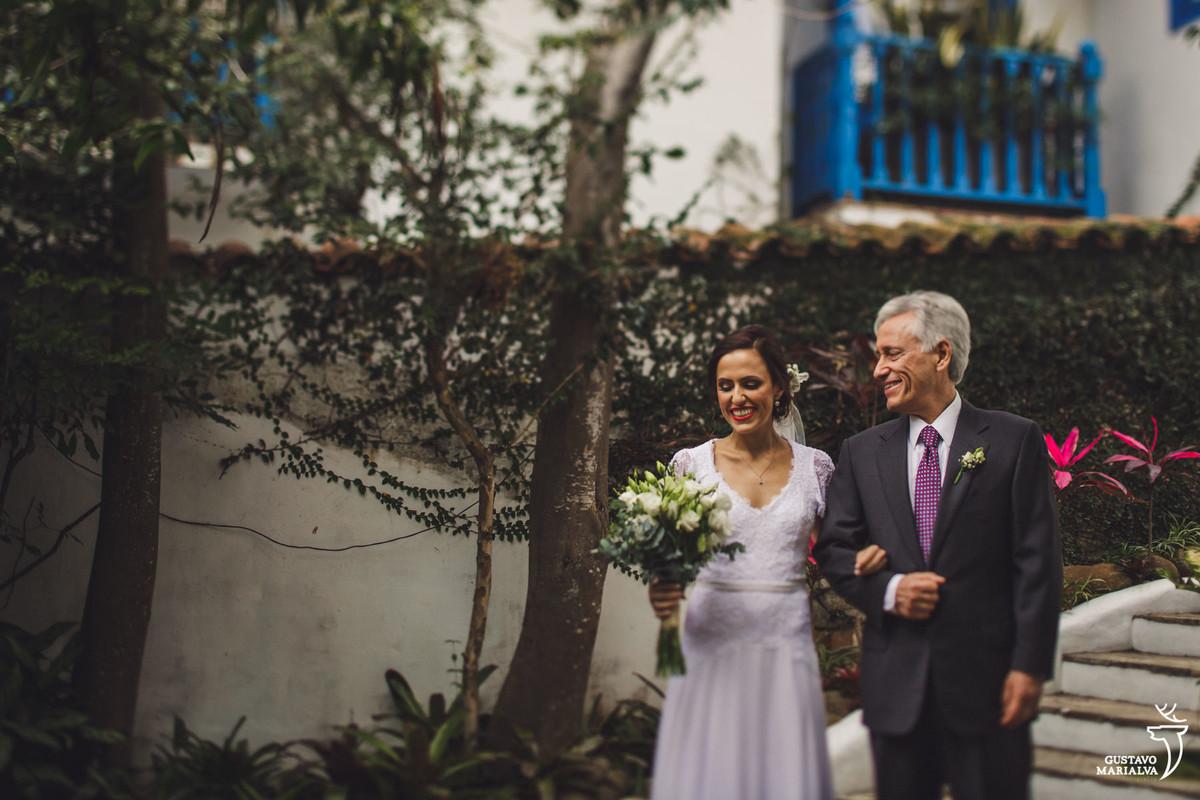 pai da noiva olha emocionado para a filha que segura o buquê sorridente