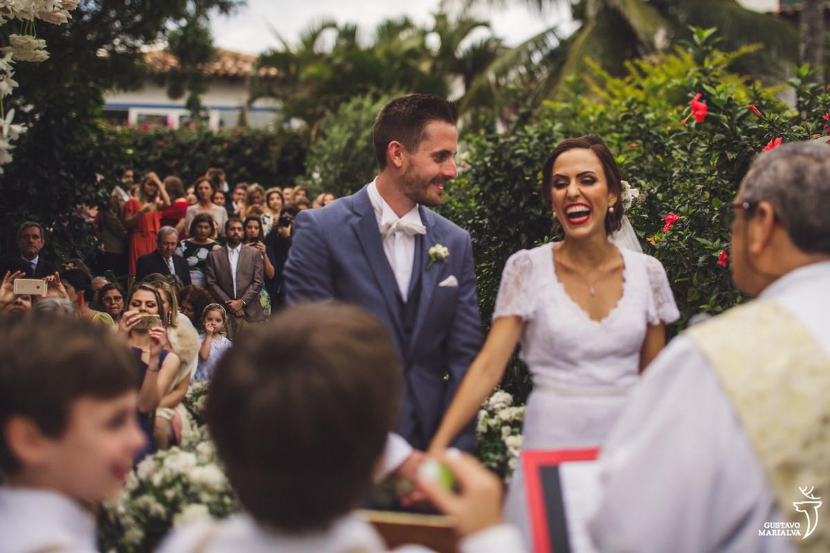 noiva sorri ao ver os pajens e é observada pelo noivo