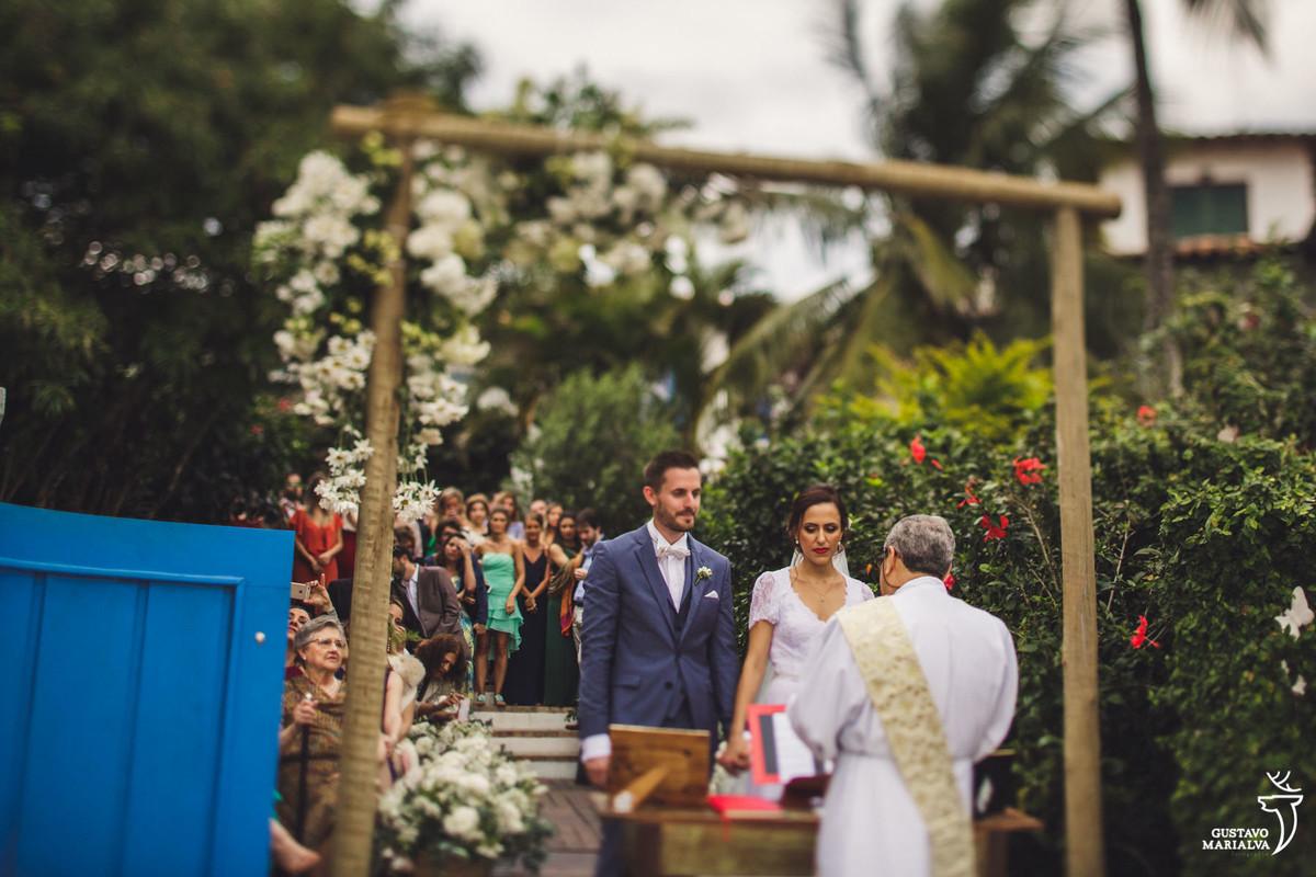 noivos observam a cerimônia com alta feito de madeira e decorado com flores no casamento em búzios
