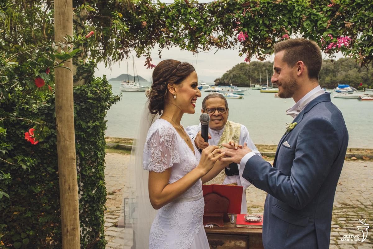 noiva coloca aliança no dedo do noivo e sorri enquanto o padre segura o microfone