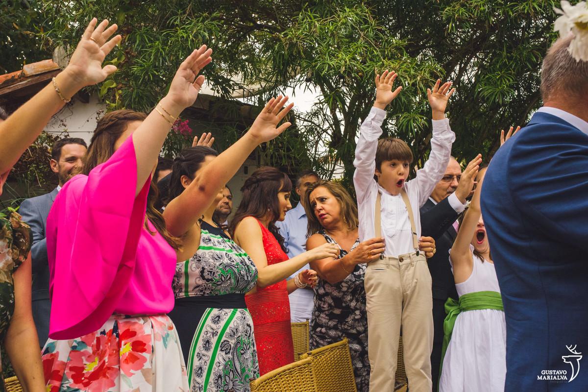 convidados levantam os braços para abençoar o casal e pajem faz careta enquanto mulher ajeita seu suspensório