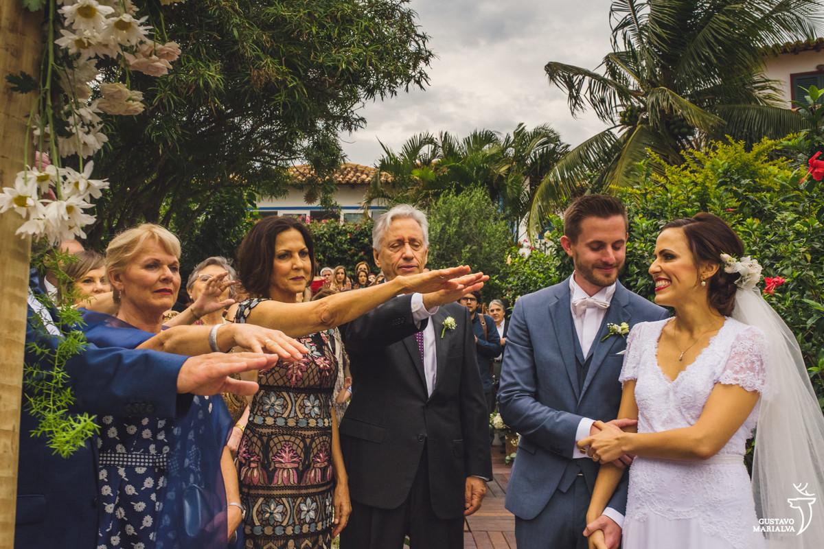 pais dos noivos estendem os braços para abençoar o casal que trocam olhares e sorriem