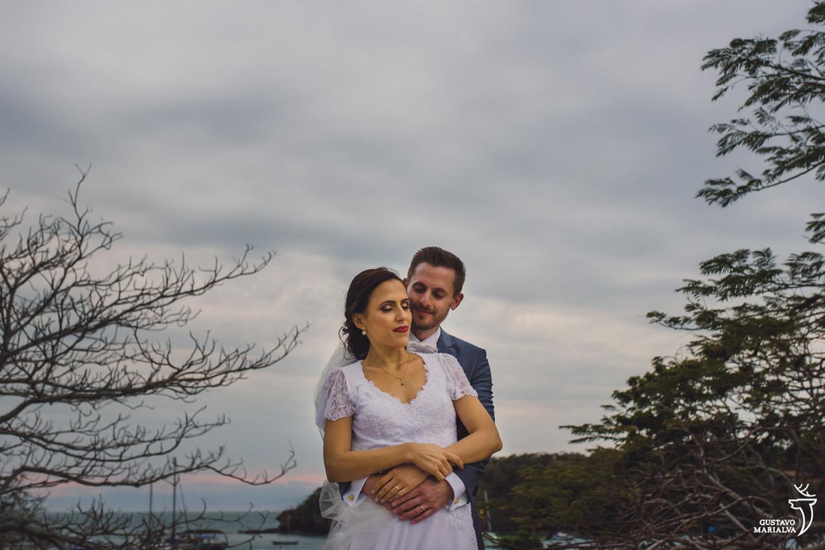 noivo abraça a noiva por trás durante retrato de casamento com a praia dos ossos em búzios ao fundo