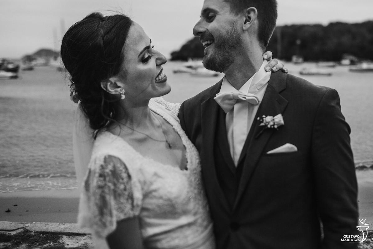 noivo usando terno azul e gravata borboleta e noiva usando vestido noivo trocam sorrisos