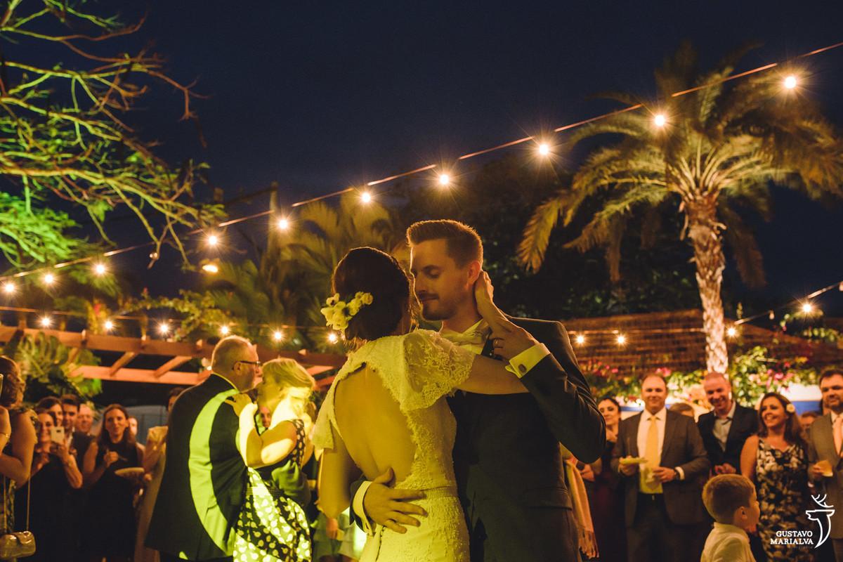 noivos faze a primeira dança abraçados com gambiarras penduradas